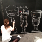 Chalkboard artist, Mallory, creates the initial background images to incorporate the actual Elan Vital plumbing fixtures. This phase is completed before the show opens.