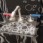 Elan Vital widespread lavatory faucet with playfully colored handles.