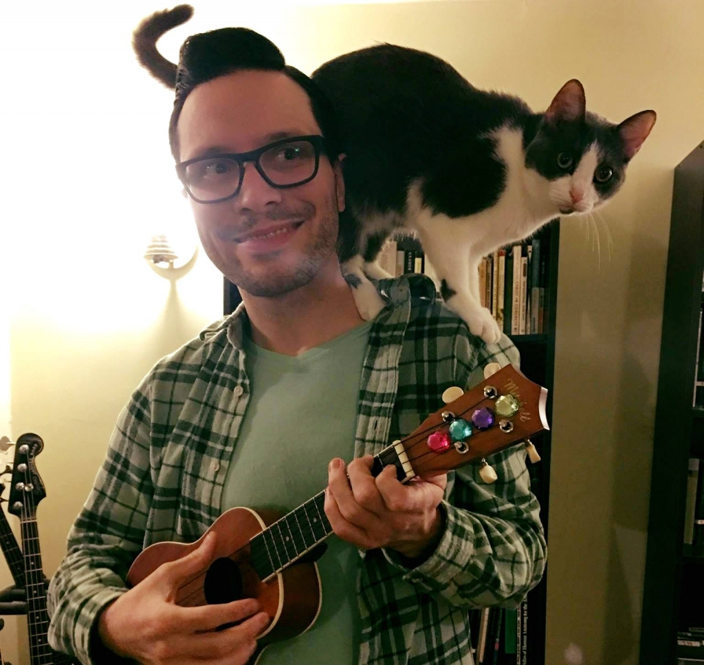 Andrew Hartwell playing ukulele with his cat