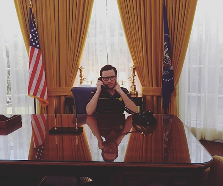 Andrew Hartwell taking a call in a replica of the 1970s oval office at the Nixon Presidential Library.